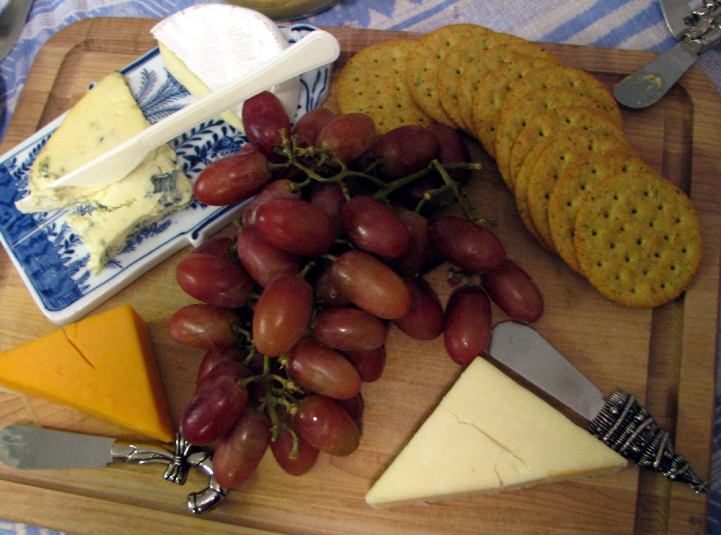 cheese and graped on a cutting board